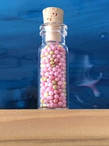 tiny corked tube with colourful contents for decoration